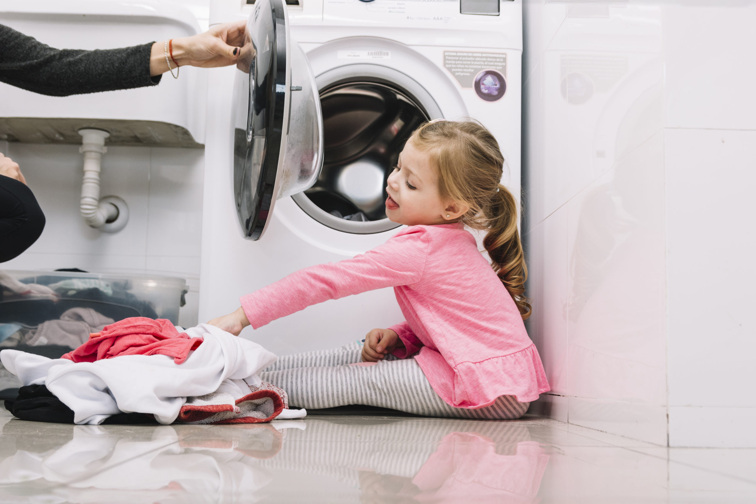 bambina mette lavatrice com la mamma